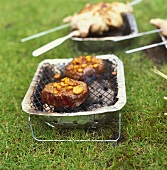 Two steaks with mango marinade on small barbecue out of doors
