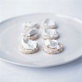 6 rice cakes spread with soft cheese on white plate