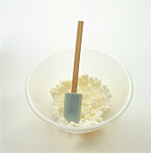 Fresh cheese in mixing bowl with spatula