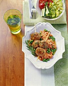 Skewered meatballs on tomato rice with peas and rosemary