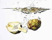 Two artichoke halves falling into water