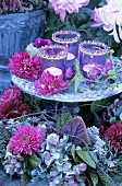Windlights, chrysanthemums and dahlias on tiered stand