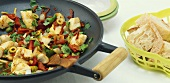 Fish stir-fry with dried tomatoes, peppers, olives & rocket