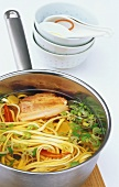 Asian noodle soup with bacon and spring onions