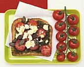 Cherry tomatoes, pesto and feta on toast