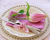 Pink napkin with lily bud on white plate