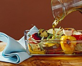 Pouring olive oil over antipasti vegetables in glass dish