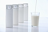 Glass of milk with milk cartons