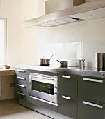 Moderne Einbauküche mit Edelstahlarbeitsplatte und Ceranfeld mit Kochtöpfen