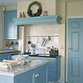 Eine Landhausküche mit blauen Einbauschränken und Dekorationsartikel