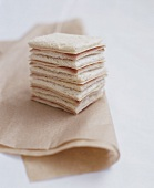 A stack of ham and cheese sandwiches on a paper napkin