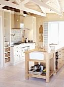 Eine Küche mit Kochinsel aus massivem Holz unter offener Fachwerkskonstruktion