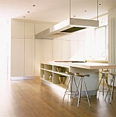 Schlichte Küche mit Einbauschränken, eine Kochinsel mit integrierter Esstischplatte und Barhockern