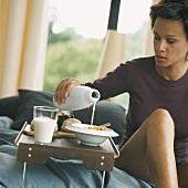Eine Frau giesst sich Milch in Cornflakes auf Bett