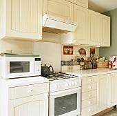 Eine weiße Landhausküche mit Gasherd und alten Geräten