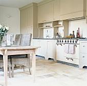Küchenzeile mit nostalgischem Herd und Holz-Hängeschränken; davor ein Esstisch mit Korbstühlen