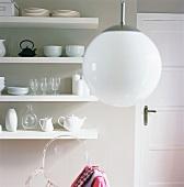 weiße Kugellampe, dahinter ein Wandregal mit Geschirr und ein durchsichtiger Plexiglasstuhl