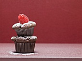 Two chocolate muffins, one on top of the other, with raspberry