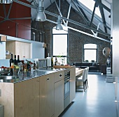 Kitchen area in high-ceilinged, open-plan interior with brick wall and gable ceiling