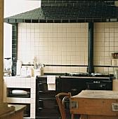 Weiss gekachelte Küche mit antikem, schwarzen Herd und schwarz gekacheltem Dunstabzug