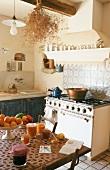 Alter Küchenherd mit blau-weiss gekacheltem Spritzschutz; darüber einen alten Kaminsims mit einer Döschensammlung