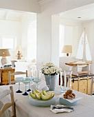 Gedeckter Esstisch in maritim dekoriertem Raum mit Tellerstapeln, Blumen in einem Zinktopf, Obst, Gebäck und Cocktailgläsern