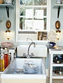 Simple, rustic kitchen with dirty plates in sink