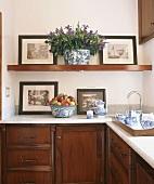 Nostalgic black and white photographs on kitchen shelf above blue and white tea service on wooden tray