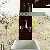 Waschbecken und Armaturen in einer Holzsäule vor Panoramafenster mit Blick auf den Wald