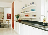 weiße Küche mit schwarzer Arbeitsfläche und rotem Wandschrank vor Esszimmer mit Holztisch
