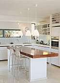 Ein Küchenblock mit Arbeitsplatte aus Holz in einer modernen, weissen Einbauküche