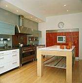 Ein massiver Küchentisch steht in der Mitte der modernen Küche mit Edelstahlelementen und rotem Einbauschrank