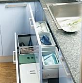 Geöffnete Schubladen mit Mülleimern & Küchenutensilien