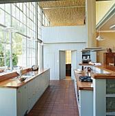 Elegante Vintageküche in Hellblau in einem Loft mit großer Industriefensterfront