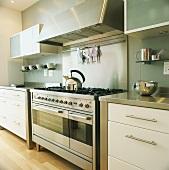 Küche mit großem Gasherd und modernen Küchenschränken mit Edelstahlflächen