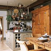 Rustikale Küche mit Kochinsel unter hängenden Kochutensilien