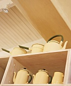 Teapots and coffeepots on shelves