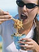 A young woman eating fried, oriental noodles with chopsticks