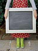 A girl wearing wellie boots holding a chalkboard
