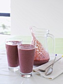 Berry smoothie in a glass jug and two glasses