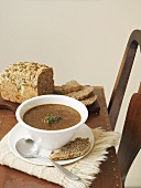 A bowl of mushroom and barley soup with bread