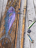 Still life with fishing tackle and fish painted on wood