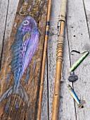 Stillleben mit Angelzubehör und auf Holz gemaltem Fisch