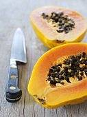 Two papaya halves and a knive on a wooden table