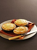 Three puff pastry pies in baking tins on a plate