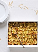 Potato gratin with feta cheese and herbs in a gratin dish