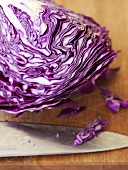 A section of red cabbage with knife on a chopping board