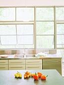 Gemüse auf einer Küchenablage in freundlicher Küche mit langer Fensterfront