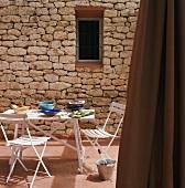 Steinfassade mit Fenster, davor weißes Gartenmobiliar und Gedeck