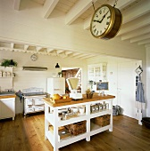 Große, weisse Küche mit Balkendecke, einer Bahnhofsuhr und einem zentralen Küchenblock in einfachem, ländlichen Stil